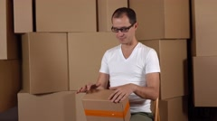 Young geeky owner of small internet store holding parcel against carton stacks Stock Footage