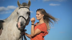 A beautiful charming blonde woman walking with a horse at a field Stock Footage