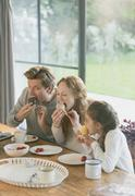 Family eating cupcakes at dining table Stock Photos