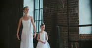Adult ballerina practicing with the little girl and trains her Russian classical Stock Footage