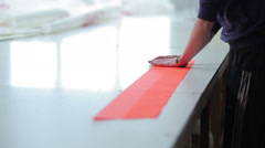 Worker smoothes orange line of cloth Stock Footage