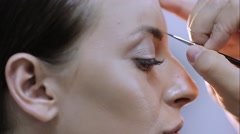 Professional make-up artist prepares a model for a photo shoot Stock Footage