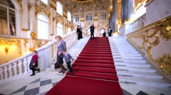 Ascending on staircase with red carpet and great windows in Hermitage Museum Stock Footage