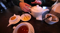 Girl is pouring tea into cup in cafe. Lemon and sugar are on the table. Stock Footage