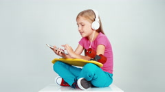 Schoolgirl 7-8 years old listening music in headphones and holds skateboard Stock Footage