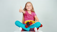 Happy school girl holding penny skateboard and sitting on floor. Thumb up. Ok Stock Footage