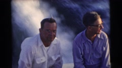 1956: middle-age men cruise the ocean in a speedboat and create ripples  Stock Footage