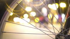 Night city life, defocused people walking street, view through bicycle wheel Stock Footage