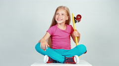 Portrait schoolgirl holds penny skateboard and sitting on floor. Thumb up. Ok Stock Footage