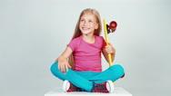Portrait schoolgirl holds penny skateboard and sitting on floor. Thumb up. Ok Stock Footage
