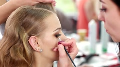Makeup eyeliner eye shadow, makeup artist stylist working with a client in the Stock Footage
