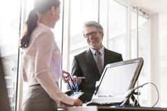 Businessman showing credentials to businesswoman at front desk Stock Photos