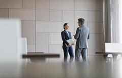 Businessman and businesswoman talking in conference room Stock Photos