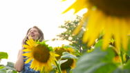 Beautiful girl talking on the phone in the field with sunflowers Stock Footage