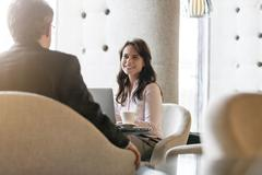 Smiling businesswoman listening to businessman in lobby Stock Photos