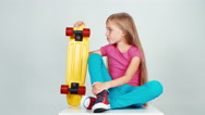 Schoolgirl 7-8 years old holds penny skateboard and sitting on the floor Stock Footage