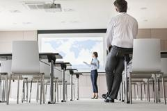 Businessman watching businesswoman leading presentation at projection screen in Stock Photos