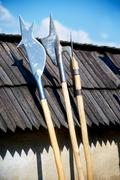 Set of middle age style weapons leaning on wooden tiled roof Stock Photos
