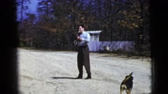 1956: a man smoking a cigarette plays catch while a dog watches FLORIDA Stock Footage
