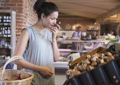 Woman grocery shopping smelling mushrooms Stock Photos