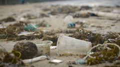 Plastic trash and waste litter on an empty beach - handheld Stock Footage