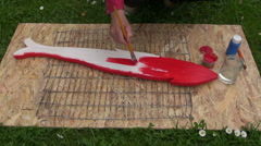 Man painting wooden fish Stock Footage