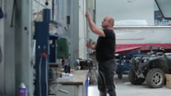 Man lifts the shutter at the yacht centre Stock Footage
