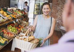 Woman with basket smiling at grocery store worker Kuvituskuvat