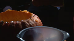 Cutting scooping meat from top cap of pumpkin into the plate Stock Footage