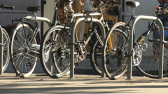 Bikes parked in front shops as pedestrians walk past Stock Footage