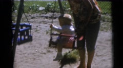 1967: three children playing on a swing set with one adult CAMDEN, NEW JERSEY Stock Footage