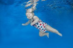 Infant swiming under water in the pool Stock Photos