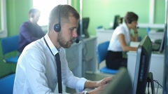 Joyful agent working in a call center with his headset Stock Footage