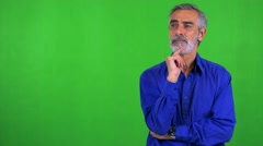 Old senior man thinks about something - green screen - studio Stock Footage