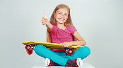 Portrait schoolgirl looking at penny skateboard and sitting on the floor Stock Footage