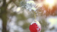 Snow drops on branch with Christmas ball slowmotion Stock Footage
