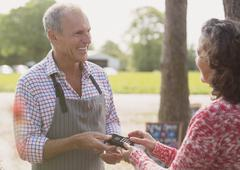 Smiling plant nursery worker offering credit card machine to customer Stock Photos