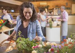 Smiling woman shopping for flowers in market Stock Photos