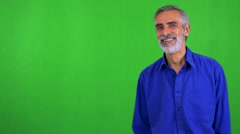 Old senior man waves with hand - green screen - studio Stock Footage