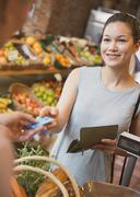 Woman paying with credit card at grocery store checkout Stock Photos