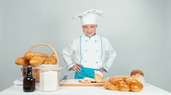 Cute baker girl standing near kitchen table with bakery products and smiling Stock Footage