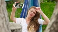 Beautiful model making selfie lying in a hammock. HD Stock Footage