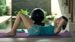 Young woman doing stomach exercise on floor on mat in luxury villa Stock Footage