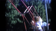 1956: two kids swinging on a swing set in the park FLORIDA Stock Footage