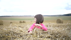 Pretty girl dabbles with a straw and smiling in a field Stock Footage