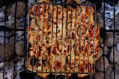 Grilling chicken on charcoal bbq Stock Photos