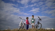 Boy with a girl holding hands, standing against the sky with bicycles Stock Footage