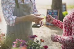 Woman paying plant nursery worker with credit card Stock Photos