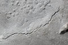A crack in the concrete. The destruction of the concrete foundation, a founda Stock Photos