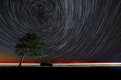 Trail stars around Polar Star above the tree near the the highway. Stock Photos